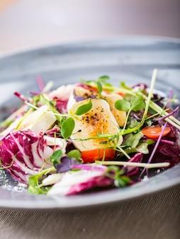ヤギのチーズとハーブの装飾が施された野菜サラダ。