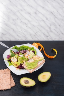 Vegetable salad with green avocado on crisp bread