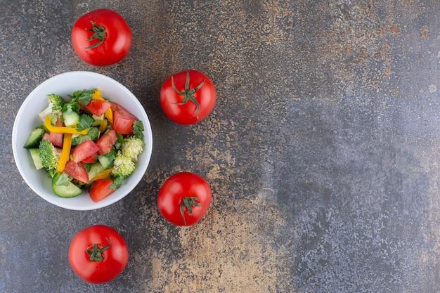 접시에 허브와 빨간 토마토를 넣은 야채 샐러드