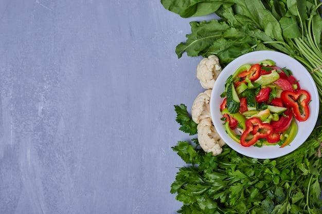 Insalata di verdure con erbe sul blu