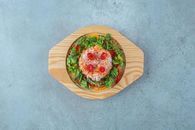 나무 접시에 허브와 함께 야채 샐러드입니다.
