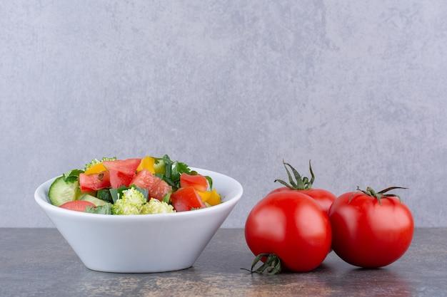 Insalata di verdure con erbe e pomodori rossi in un piatto