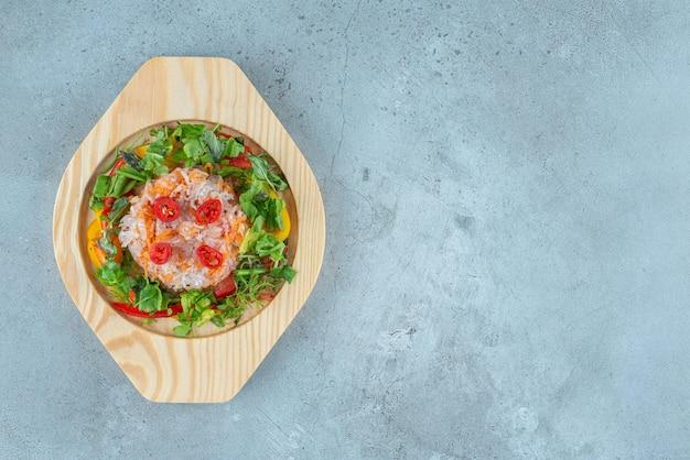 Insalata di verdure con erbe aromatiche in un piatto di legno.