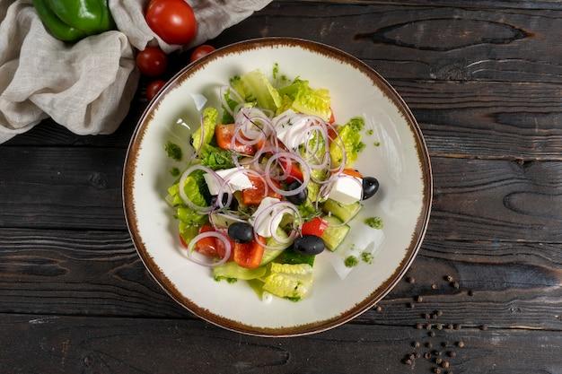 レタス、オリーブ、赤ピーマン、チェリートマト、オニオンリング、キュウリ、フェタチーズの野菜サラダ。