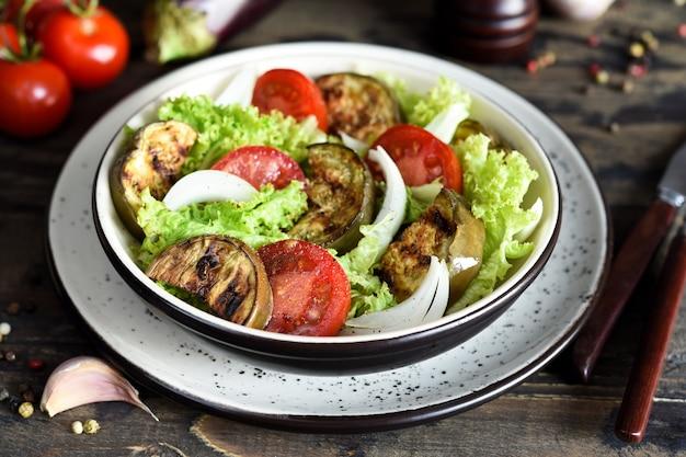 Овощной салат с листьями салата, помидорами и жареными баклажанами на кухонном столе.