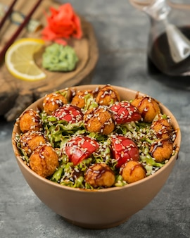 Vegetable salad with meatballs, tomato,and herbs inside bamboo bowl.
