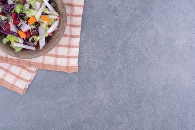 Овощной салат со смешанными ингредиентами на клетчатом кухонном полотенце