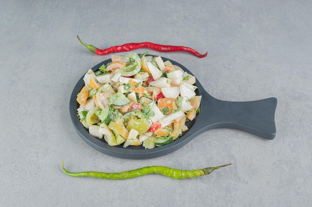 Vegetable salad with mixed ingredients on a wooden board.