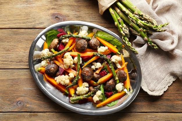 Овощной салат с грибами и молодой морковью на деревянном столе, вид сверху