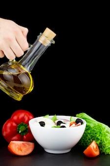 ボトルからオリーブオイルを注いだ野菜サラダ。