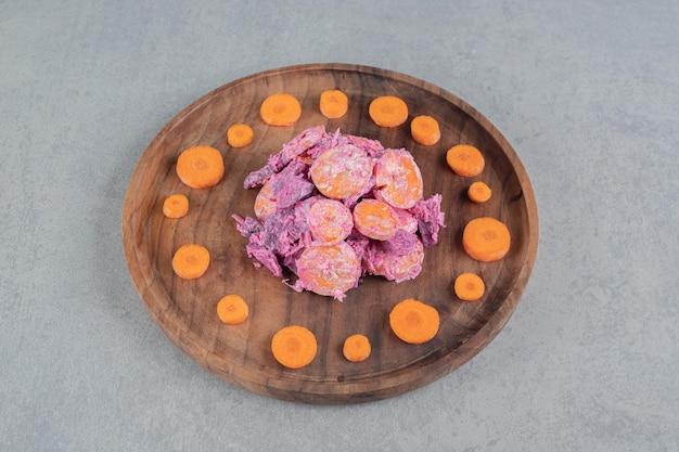 보라색 비트 뿌리와 오렌지 다진 당근을 사워 크림과 섞은 야채 샐러드.