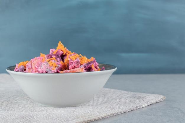 Insalata di verdure con barbabietole viola e carote tagliate all'arancia mescolate a panna acida.