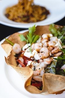 Vegetable salad with shrimps in tortilla bowl