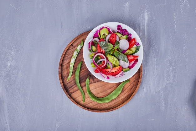 Insalata di verdure con cibi affettati e tritati in un piatto bianco all'interno del vassoio in legno.