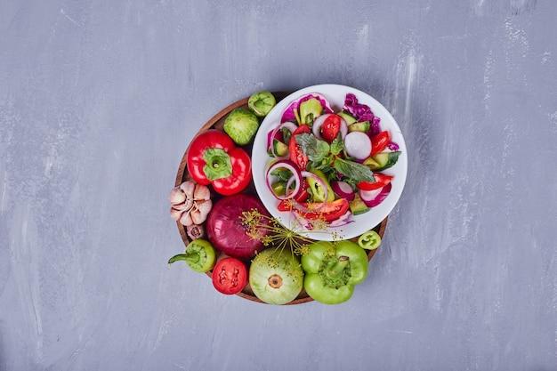 Insalata di verdure con cibi affettati e tritati in un piatto bianco, vista dall'alto.