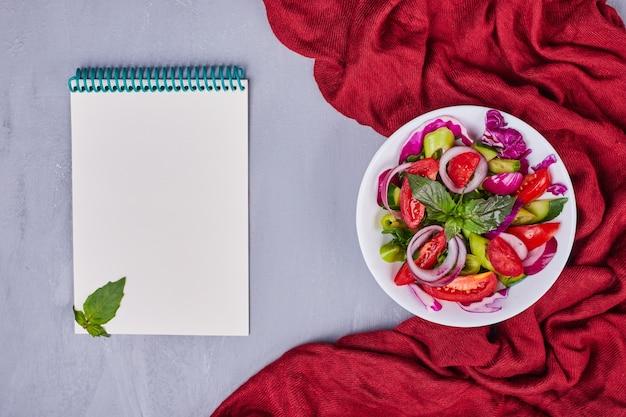 Insalata di verdure con cibi affettati e tritati in un piatto bianco con un ricettario da parte.
