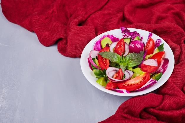 Insalata di verdure con cibi affettati e tritati in un piatto bianco.