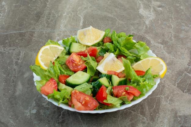 하얀 접시에 레몬 조각과 야채 샐러드. 고품질 사진