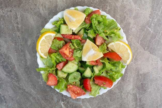 Овощной салат с ломтиками лимона на белой тарелке