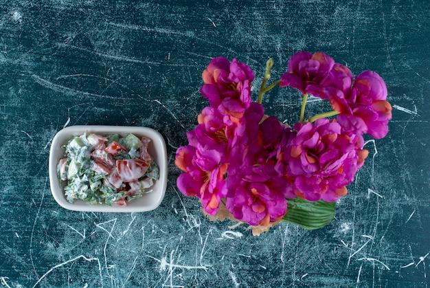 하얀 접시에 사워 크림을 곁들인 야채 샐러드. 고품질 사진