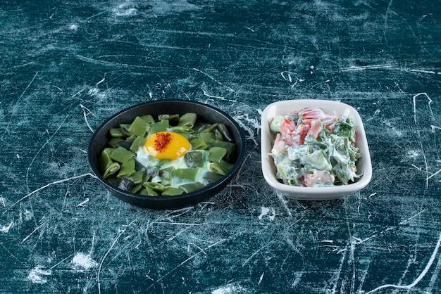 目玉焼きと豆を添えた白い皿にサワークリームを添えた野菜サラダ。高品質の写真