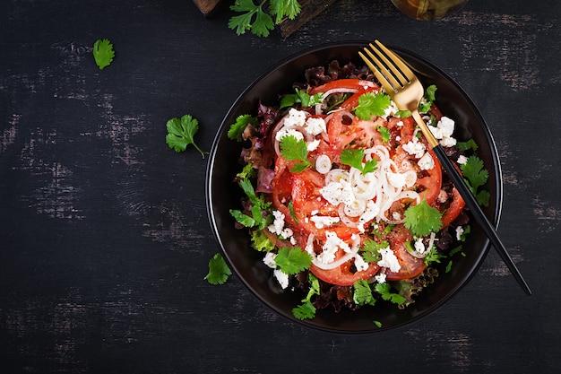 Овощной салат с помидорами, свежим салатом, мягким сыром и луком. здоровое диетическое питание. вид сверху, вверху