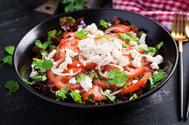 Овощной салат с помидорами, свежим салатом, мягким сыром и луком. здоровое диетическое питание.