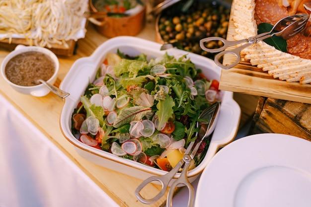 Овощной салат с томатным редисом и листьями салата на блюде с сырно-колбасными нарезками и оливками