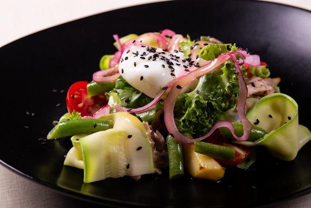 Овощной салат с помидорами и семенами чиа на черной тарелке