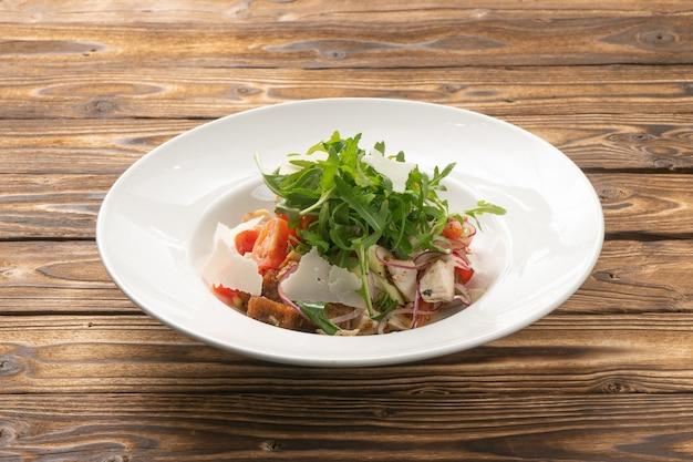 Овощной салат с помидорами, рукколой, курицей, пармезаном и ржаными гренками в белой керамической тарелке