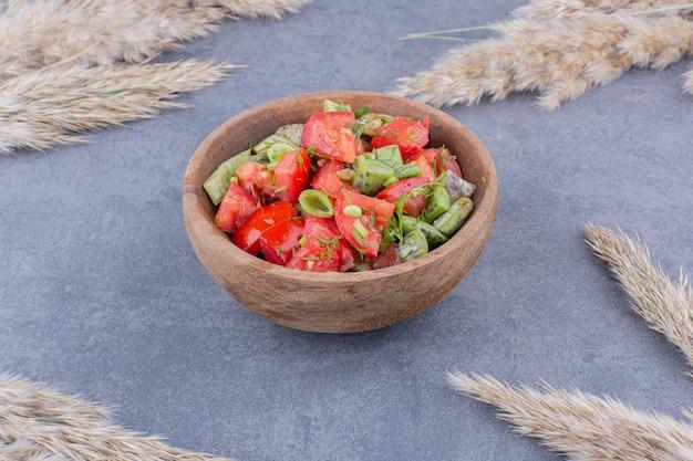Insalata di verdure con pomodori e fagiolini all'interno di un piatto