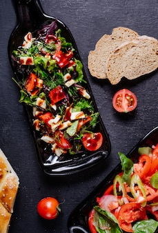 Vegetable salad with tomatoes inside black bottle platter.