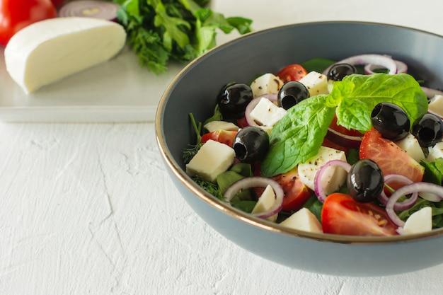 Овощной салат с помидорами, оливками, луком, перцем, сыром фета, листьями салата. салат хориатики