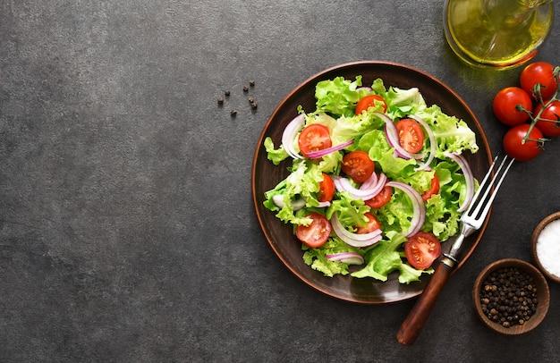 黒にトマト、赤玉ねぎ、ソースの野菜サラダ、上面図
