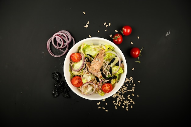 Vegetable salad with tuna and side onion slices top view