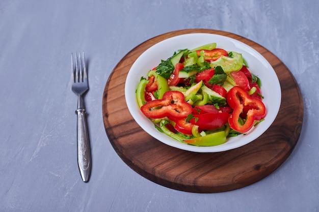 Vegetable salad on wooden board on blue