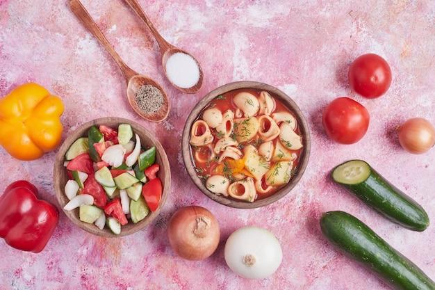Insalata di verdure in una tazza di legno con una ciotola di zuppa di pasta.