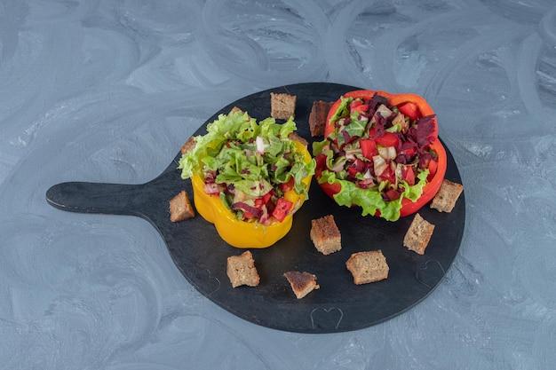 Insalate di verdure porzionate in fette di peperone su un vassoio da portata sul tavolo di marmo.