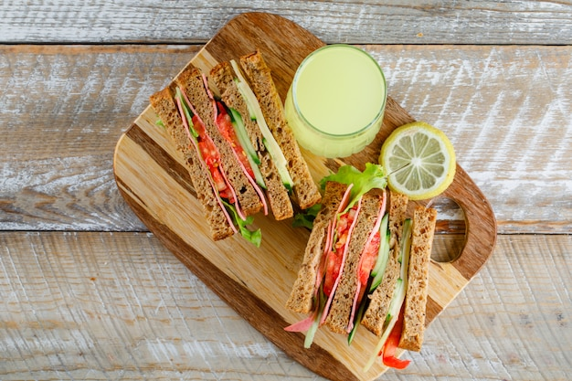 Vegetable sandwich with cheese, ham, lemonade flat lay on wooden and cutting board