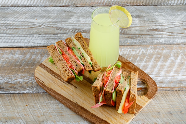 Vegetable sandwich with cheese, ham, lemonade on wooden and cutting board, high angle view.