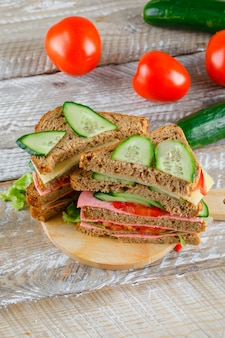 Vegetable sandwich with cheese, ham on wooden and cutting board, high angle view.
