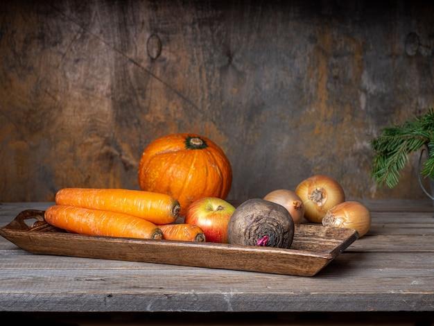 소박한 요리 테이블에 생 야채 세트 긴 나무 쟁반에 사탕무 당근