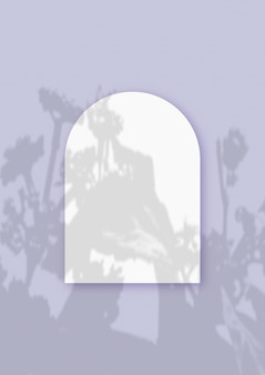 Растительные тени, наложенные на лист в виде арки из фактурной белой бумаги на фиолетовом фоне стола