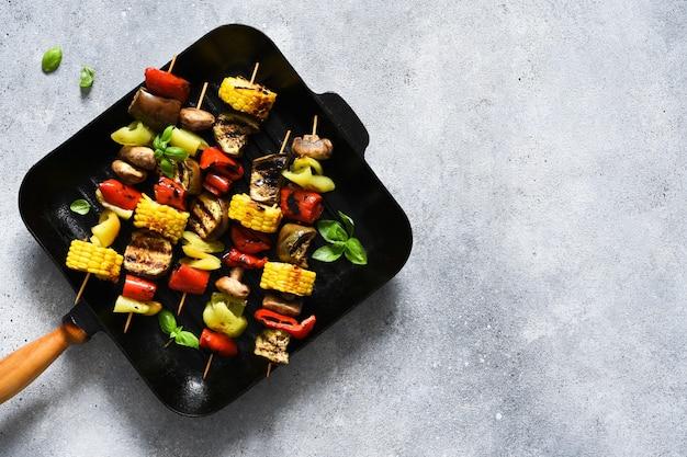 Овощной шашлык на вертеле в сковороде для гриля на бетонном фоне. овощи обжарить на сковороде.