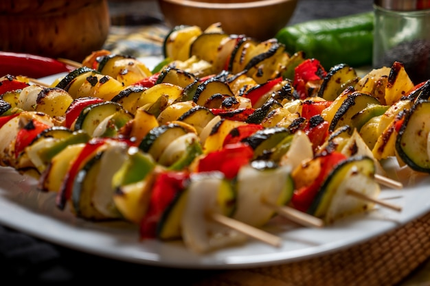 Vegetable skewers in a white plate with some raw ingredientes around