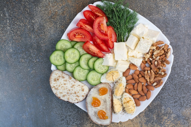 Vegetable slices, eggs, cheese and nuts on white plate.