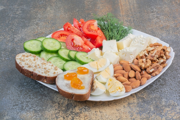 Vegetable slices, eggs, cheese and nuts on white plate