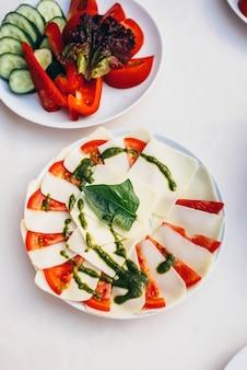 モッツァレラチーズとトマトのスライスの横にあるキュウリ、トマト、ピーマン、レタスの野菜スライスとペストソース