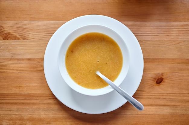 茶色の木製テーブルの上に立っているスプーンと白いボウルの野菜スープ
