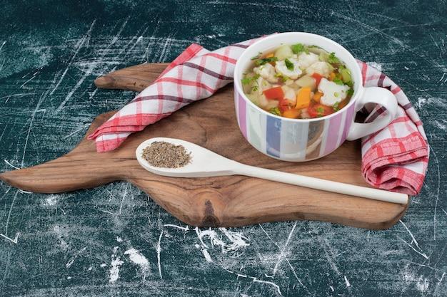 テーブルクロスとスプーンで木の板に野菜スープ。高品質の写真